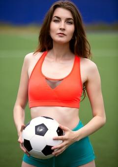 Een vrouwelijke voetballer in een top en korte broek heeft een bal in haar handen