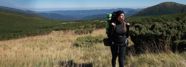 Een vrouwelijke wandelaar staat tegen de achtergrond van een berglandschap en kijkt opzij