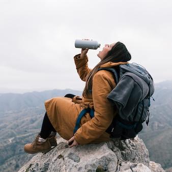 Een vrouwelijke wandelaarzitting bovenop berg die het water van fles drinkt