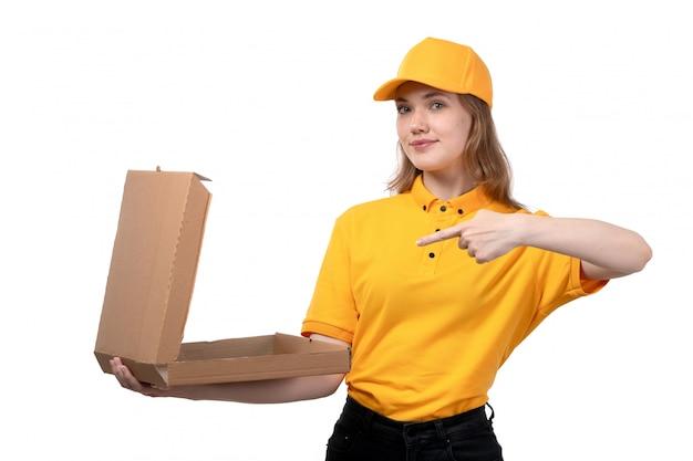Een vrouwelijke werknemer van de vooraanzicht jonge vrouwelijke koerier die van de dienst van de voedsellevering een lege pizzadoos op wit houden