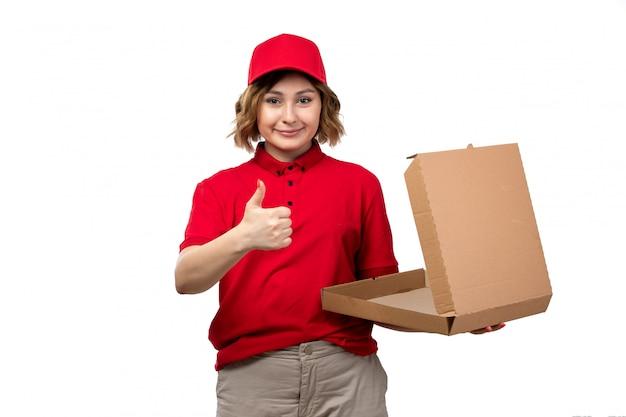Een vrouwelijke werknemer van de vooraanzicht jonge vrouwelijke koerier van de dienst die van de voedsellevering een lege pizzadoos houdt die op wit glimlacht