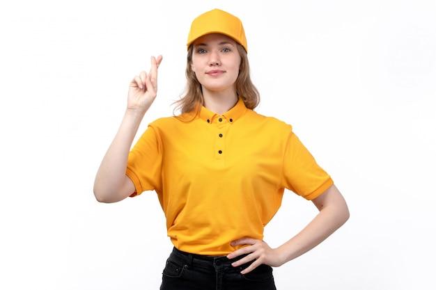 Een vrouwelijke werknemer van de vooraanzicht jonge vrouwelijke koerier van de dienst die van de voedsellevering gekruiste vingers tonen die op wit glimlachen