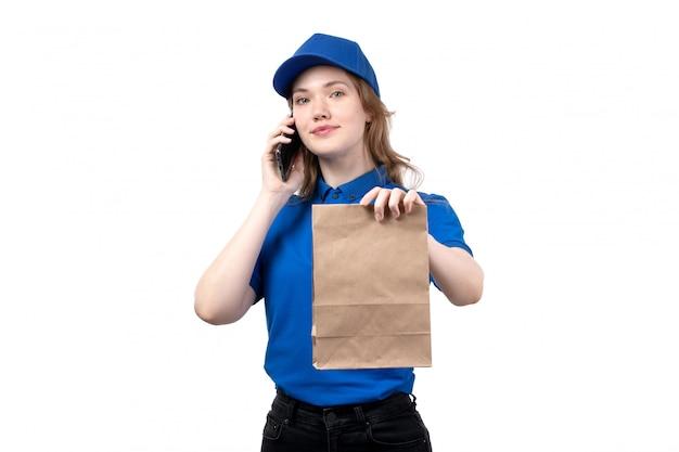 Een vrouwelijke werknemer van de vooraanzicht jonge vrouwelijke koerier van de dienst die van de voedsellevering op telefoon spreekt en voedselpakket op wit houdt