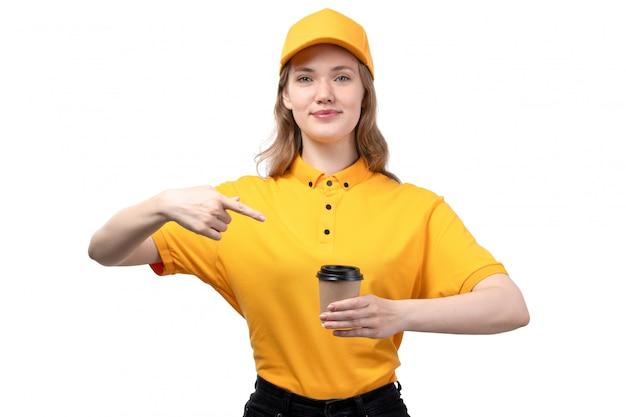 Een vrouwelijke werknemer van de vooraanzicht jonge vrouwelijke koerier van de dienst van de voedsellevering het glimlachen de koffiekop van de holding op wit