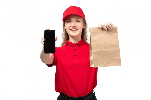 Een vrouwelijke werknemer van de vooraanzicht jonge vrouwelijke koerier van de dienst van de voedsellevering het glimlachen het pakket van de holdingslevering en smartphone op wit