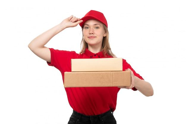 Een vrouwelijke werknemer van de vooraanzicht jonge vrouwelijke koerier van de dienst van de voedsellevering het glimlachen holdingsdozen met voedsel op wit