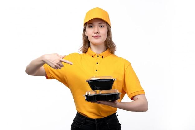 Een vrouwelijke werknemer van de vooraanzicht jonge vrouwelijke koerier van de dienst van de voedsellevering het glimlachen holdingskom met voedsel dat op wit glimlacht