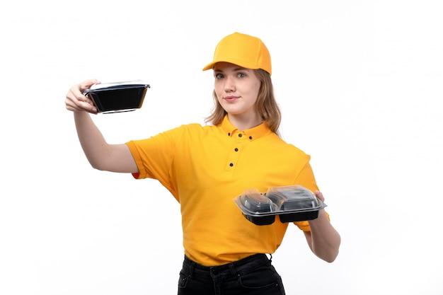 Een vrouwelijke werknemer van de vooraanzicht jonge vrouwelijke koerier van de dienst van de voedsellevering het glimlachen holdingskommen met voedsel op wit