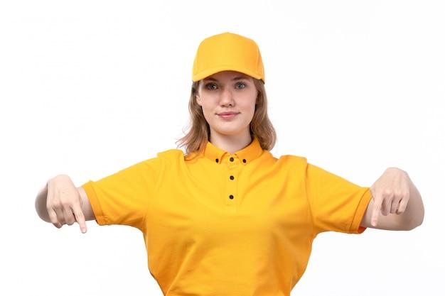 Een vrouwelijke werknemer van de vooraanzicht jonge vrouwelijke koerier van de dienst van de voedsellevering het glimlachen wijzend op met haar vingers op wit