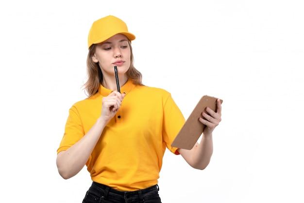 Een vrouwelijke werknemer van de vooraanzicht jonge vrouwelijke koerier van de holdingspen en blocnote van de voedselleveringsdienst voor handtekeningen die op wit denken
