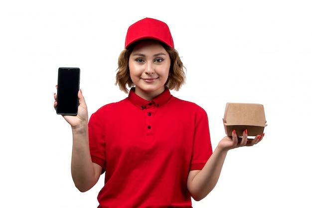 Een vrouwelijke werknemer van de vooraanzicht jonge vrouwelijke koerier van van de de leveringsdienst van de voedsellevering het pakket van de het voedsellevering en smartphone op wit