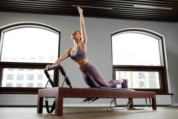 Een vrouwelijke yoga-instructeur traint op een hervormde cadilac in een grote hal tegen een raam, moderne apparatuur voor training in sportscholen, correctie van het bewegingsapparaat.