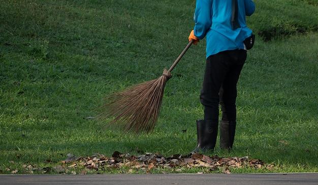 Een vrouwenarbeider veegt bladeren in het openbare park