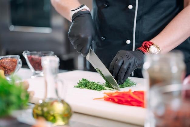 Een vrouwenchef-kok snijdt groenten in de keuken in een restaurant