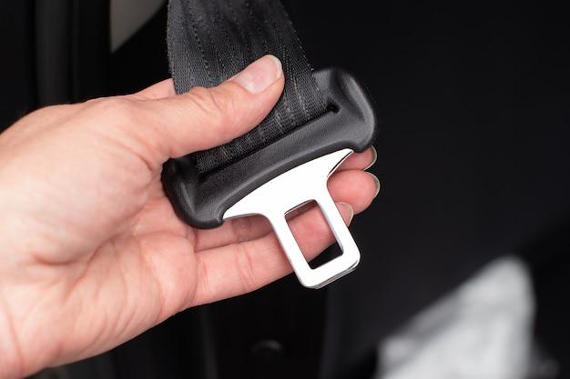 Een vrouwenhand die de veiligheidsgordel vastmaakt terwijl ze in een auto zit voor de veiligheid voordat ze op de weg rijdt