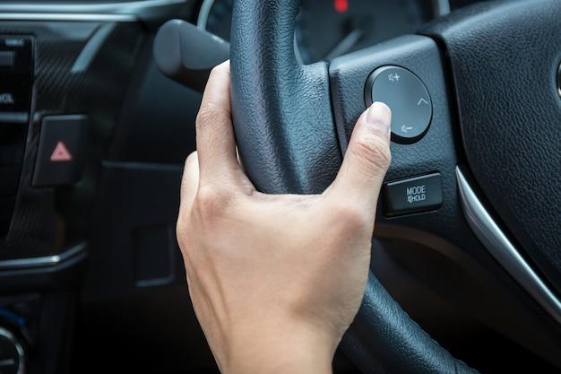 Een vrouwenhand duwt de volumecontroleknop op een stuurwiel.