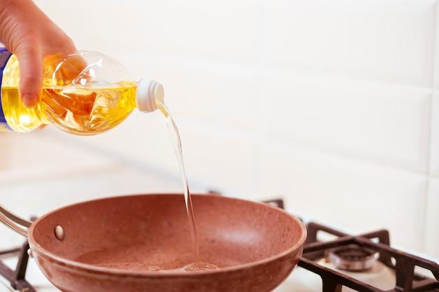 Een vrouwenhand giet thuis bakolie op de pan