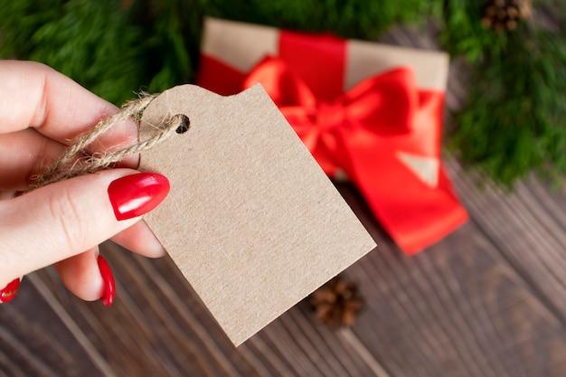 Een vrouwenhand houdt een label met ruimte voor tekst vast tegen de achtergrond van het geschenk in een pakket