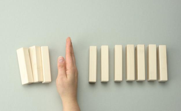 Een vrouwenhand tussen de houten blokken voorkomt dat het meeste valt. het concept van verzekeren, een sterke leider die voorkomt dat het bedrijf failliet gaat