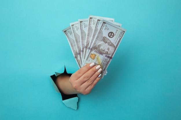 Een vrouwenhand verschijnt in het gat in gescheurd papier en perst dollarbiljetten. het concept van alimentatie, armoede, uitkeringen, studiebeurzen en gierigheid