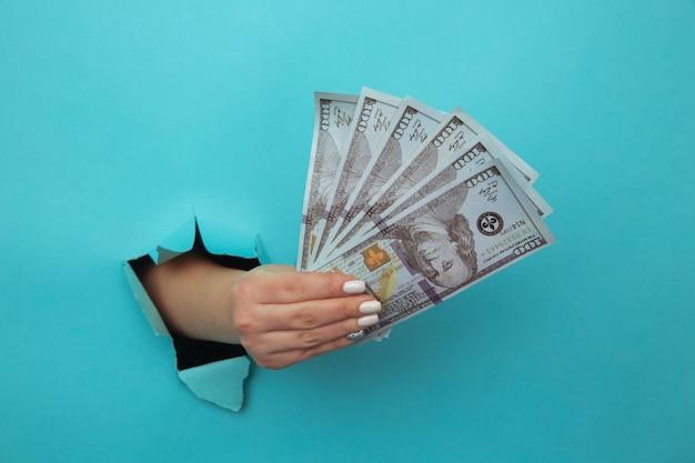 Een vrouwenhand verschijnt in het gat van gescheurd blauw papier en perst dollarbiljetten. het concept van alimentatie, armoede, uitkeringen, studiebeurzen en gierigheid