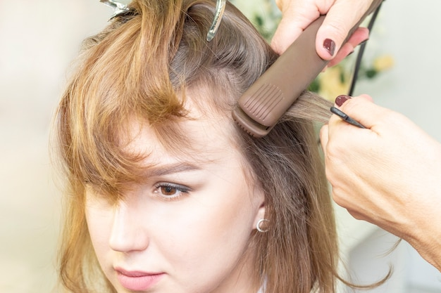 Een vrouwenkapper in de salon die het haar van een mooi jong meisje kamt. op tafel liggen gereedschappen en cosmetica voor haar. haarverzorging concept, kappers