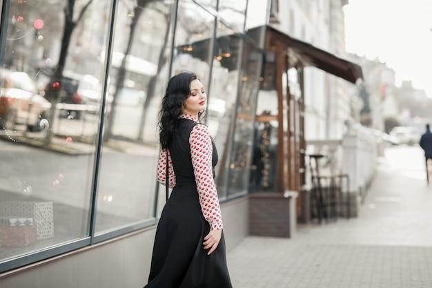 Een vrouwenmannequin loopt door de straten van de stad in de buurt van moderne gebouwen