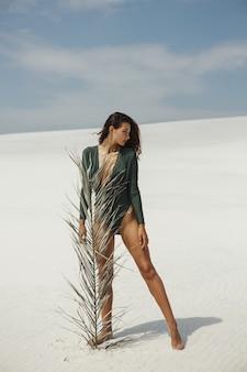 Een vrouwenmodel dat een modieus zwempak draagt dat zich met palmblad tegen zand bevindt