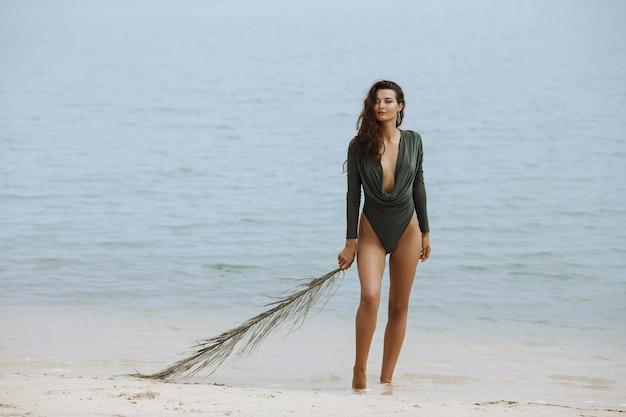 Een vrouwenmodel dat een modieus zwempak draagt, palmblad vasthoudt en tegen zee staat