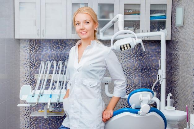 Een vrouwentandarts in witte uniform vormt tegen een van tandheelkundige apparatuur in een tandartspraktijk