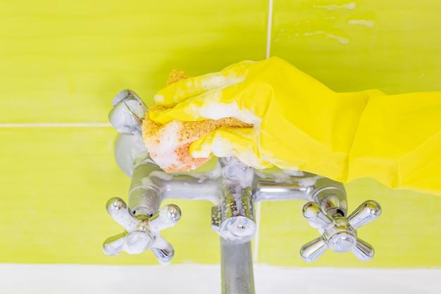 Een vrouwtje dient een gele latexhandschoen in met een badmixer. veel schuim. het concept van het schoonmaken van de badkamer, netheid. copyspace.