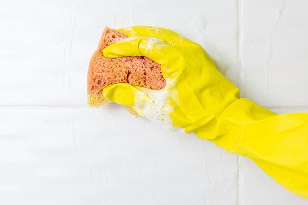 Een vrouwtje hand in een gele latex handschoen sponzen een tegel. er zit veel schuim in de gootsteen. het concept van het schoonmaken van de badkamer, netheid. copyspace.
