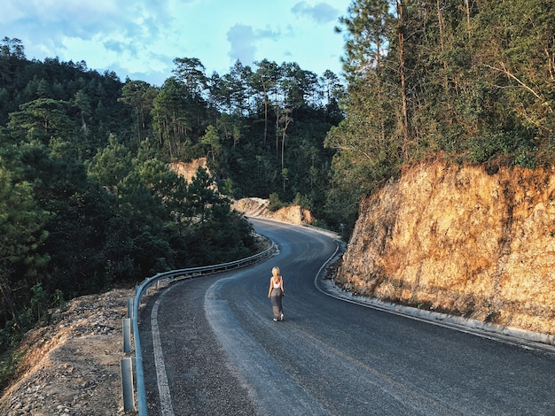 Een vrouwtje op een smalle bochtige weg