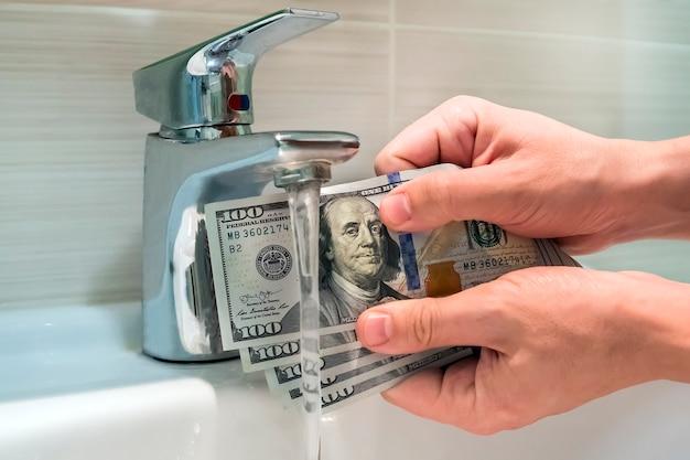 Een vuile amerikaanse honderd dollar biljet schoonmaken. geld op de zwarte markt. bankbiljetten van 100 dollar in de handen van mannen in de buurt van waterstralen in wastafel.