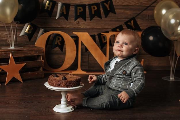 Een vuile jarige in een grijs pak eet een chocoladetaart op een bruine achtergrond