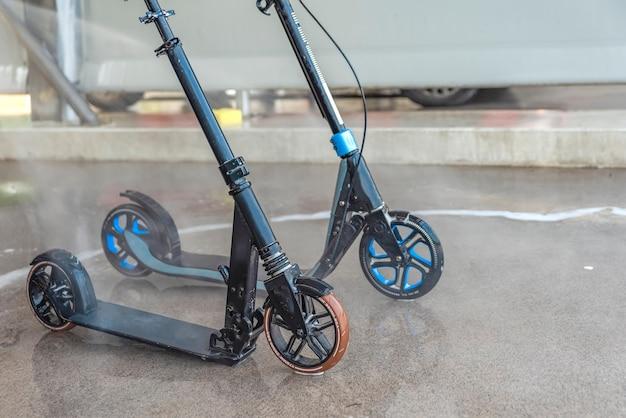 Een vuile scooter wassen bij een wasstraat onder hoge druk. onderhoud en reiniging van de scooter.