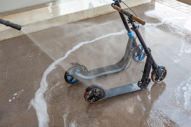 Een vuile scooter wassen bij een wasstraat onder hogedrukwater verzorging en reiniging van de scooter