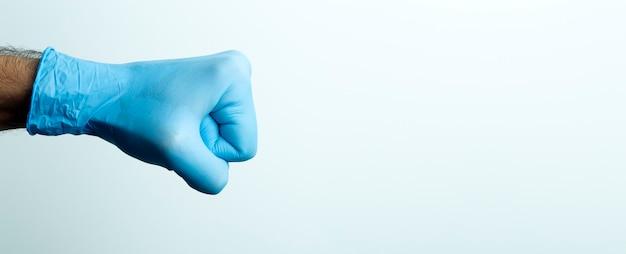 Een vuist in een medische handschoen. doctor's hand in een blauwe medische handschoen op een lichte achtergrond.