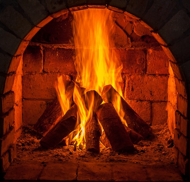 Een vuur brandt in een open haard