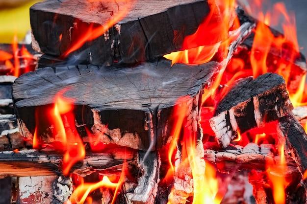 Een vuur met kolen en vuur op de achtergrond van de natuurpicknick. verbrandt een vreugdevuur voor eten op straat