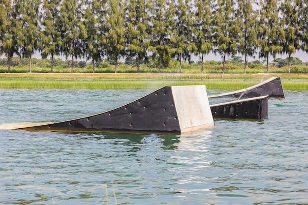 Een wakeskater glijdt over een enorm zwevend spoorhindernis achter een boot