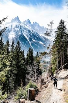 Een wandelaar die op een heuvel met een rotsachtige berg loopt