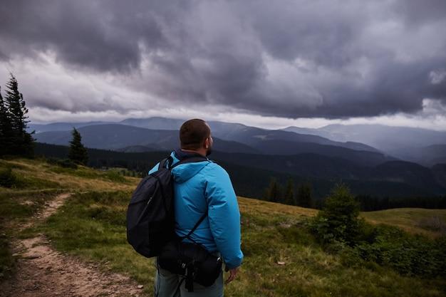 Een wandelaar die zich op een bergweide bevindt. genieten van uitzicht voor de storm. wandelen in de karpaten
