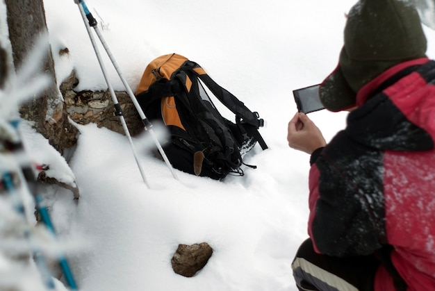 Een wandelaar maakt foto's met een smartphone een gewone woelmuis die plotseling op zijn rugzak klom