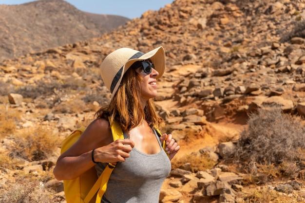 Een wandelaar met een gele rugzak die langs het canyonpad loopt naar de mirador de la peñitas, fuerteventura, canarische eilanden. spanje