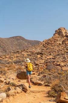 Een wandelaar met een hoed en een gele rugzak die langs het canyonpad loopt naar de mirador de la peñitas, fuerteventura, canarische eilanden. spanje