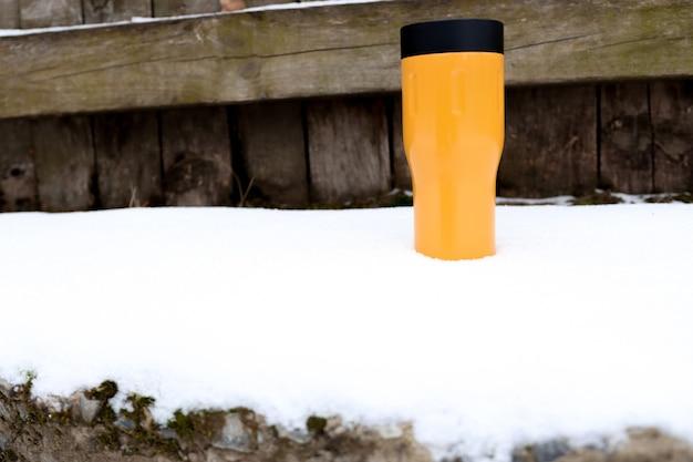 Een warme drank in een thermoskan staat op de sneeuwthermos van felle kleur op straat bij ijzig weer