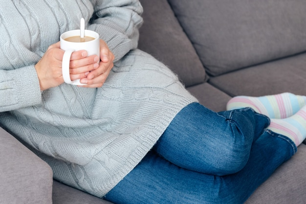 Een warme kop koffie drinken op de bank