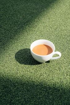 Een warme kop koffie op een koude ochtend, op groen gras met dauwachtergrond