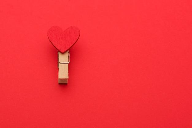 Een wasknijper met liefde op een rode achtergrond